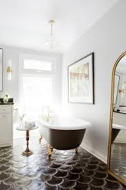 black cement floor tiles with black and gold clawfoot tub