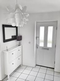 white hallway with white tiles with ikea hemnes shoe cabinet and