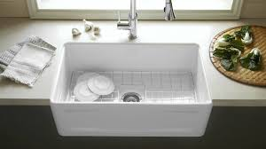 white farmhouse sink with rack inside the basin for modern kitchen