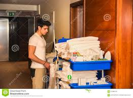 House Keeping by Young Man Pushing A Housekeeping Cart In A Hotel Stock Photo