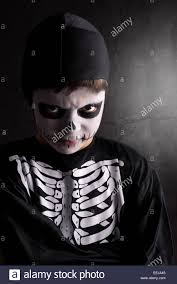 skeleton faces halloween boy with face paint and skeleton halloween costume isolated in a