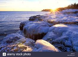 lake superior ice covered rocky shore at sunrise grand marais mn