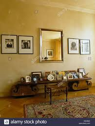 Low Console Table Framed Black White Photographs On Either Side Of Mirror Above Low