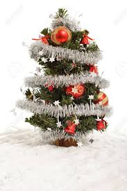 small decorated christmas tree in artificial snow isolated stock