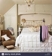 brown velvet armchair beside brass bed with white bedlinen in