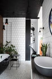 black and white bathroom with copper wall plants black