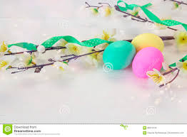 wooden easter eggs that open easter eggs and apple tree branch on white wooden background