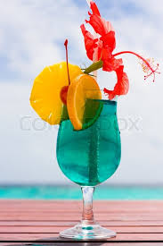 cocktail on a beach table with a tropical fruit stock photo