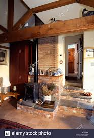 black cast iron stove in cottage hall with beams and exposed brick