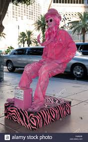 invisible halloween costume street artist dressed in pink sitting on an invisible chair las