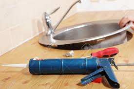 Sealant For Kitchen Sink by Caulking Gun With Silicone Sealant Against Kitchen Sink