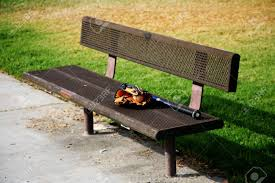 lonely metal bench with a baseball glove and mitt on it stock