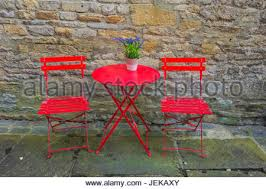 Red Metal Chair Two Blue Metal Chairs And Table Standing Outside The Entrance Of