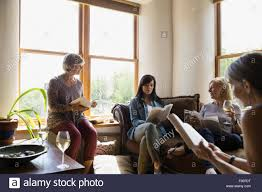 women drinking wine book club in living room stock photo royalty