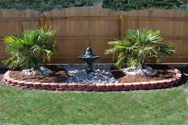 black faux stone water fountain combined with two palm trees