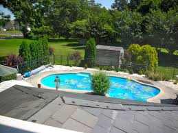 modern and small swimming pool in backyard with terrace white