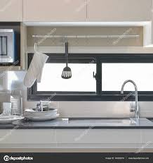 up modern kitchen ceramic ware and utensils setting up next to sink in modern
