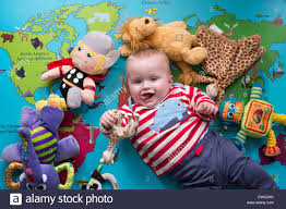 a young baby boy plays with toys on a soft play map of the world