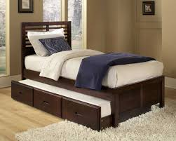 varnished dark walnut wood single bed trundle bed placed on the