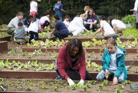michelle obama plants vegetables with a bunch of cute kids in the