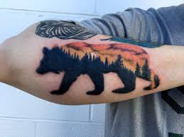 bear and forest silhouette with sunset tattoo done by chris