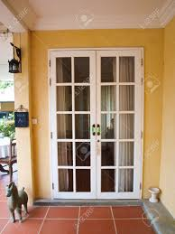 double patio white french doors with windows on yellow wall stock