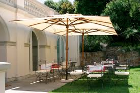 spacious outdoor living space with two rectangle umbrellas and