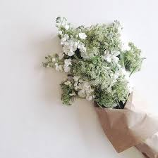paper wrapped flowers intricate white blooms light green bouquet wrapped in brown paper