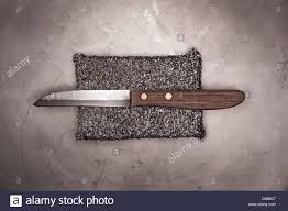 old kitchen knife with silver sponge on metal surface stock photo