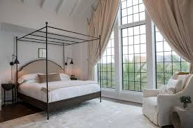 wood and iron canopy bed with curved headboard transitional