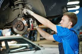 car suspension repair car mechanic replacing car wheel brake shoes of lifted automobile