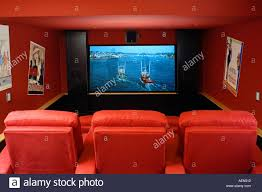 luxury home movie theater and screen red recliner chairs stock