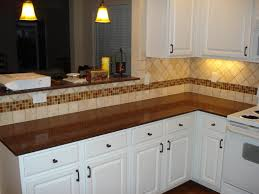 tumbled marble backsplash with multi colored glass accent strip