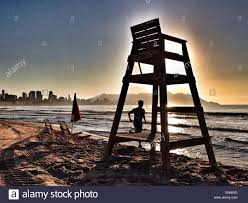 Chairs On A Beach Lifeguards Chair On A Beach At Sunrise With Runner Passing By