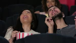 couple in cinema theater watching a movie they eating popcorn
