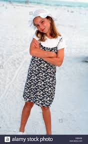 10 year old on beach wearing sunhat and sun dress stock