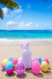 Beach Color by Easter Bunny And Color Eggs On The Sandy Beach By The Ocean Stock