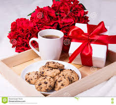 flowers and chocolate wooden tray with chocolate chip cookies cup of tea flowers and