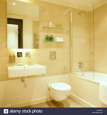 mirror above rectangular basin in modern city bathroom with toilet mirror above rectangular basin in modern city bathroom with toilet beside bath with glass shower screen