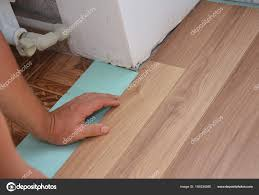 renovating a house man installing laminate wood flooring in problem area worker