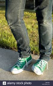 Skinny Jeans And Converse A Teenage Girls Legs Wearing Skinny Blue Denim Jeans And Green