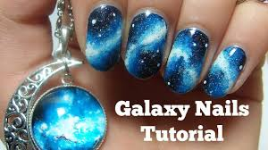 blue and black galaxy nail art with white stars design