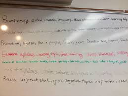 student writing paper reflecting on processes building and tutoring another word a sample of the white board with student writing process details photo by angela