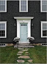 love the blue door here with the white trim against the dark house