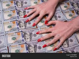 woman u0027s hands with red nails lying on the money greed for money