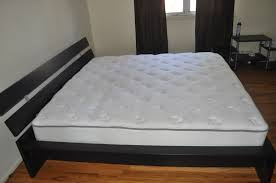 black partecle board bed frame with headboard and white mattress
