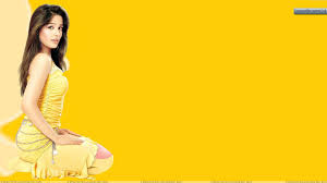 amrita rao sitting in yellow dress and background wallpaper