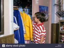 boy choose select decide shirt clothes wear closet hang neat clean