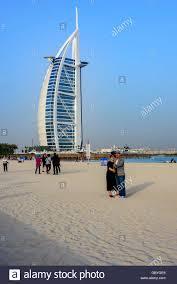 asian tourists taking selfies in front of burj al arab dubai