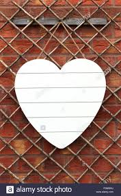 white shabby chic wooden heart hanging on a trellis set against a